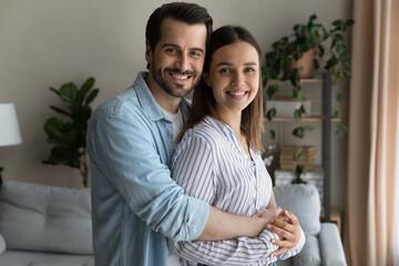 Loving husband hugs beloved wife smiling look at camera enjoy harmonic relation, happy marriage,...