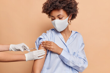 Obraz Coronavirus protection and mass immunization concept. Serious curly haired woman wears protective face mask against virus wears blue shirt receieves inoculation in shoulder isolated on beige wall - fototapety do salonu