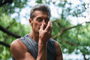 Fototapeta Man keeping his eyes closed and doing breathing exercise while closes nostril with finger obraz