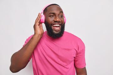 Indoor shot of happy black man has upbeat mood listens music via wireless headphones enjoys...