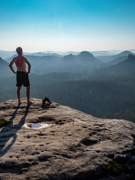 Naked man with a sporty figure on the edge of a rock enjoys the view of the morning landscape.