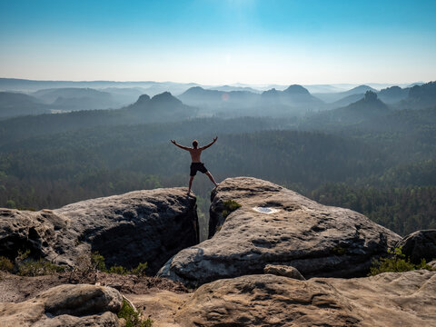 Shirtless male silhouette with raised arms on sharp mountain top.