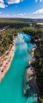 vertical shot of a blue lake surrounded with green trees on a sunny day with white and blue skies