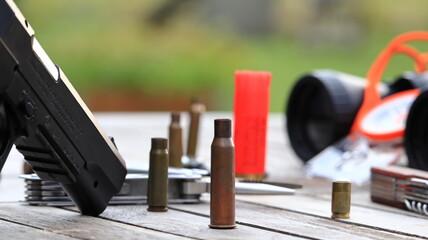 Fototapeta Pistolet i naboje, łuski do pistoletu. Wiatrówka i lornetka obraz