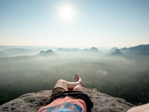 Hiker and hiker with bare feet lie on the edge of a rock massif and relax