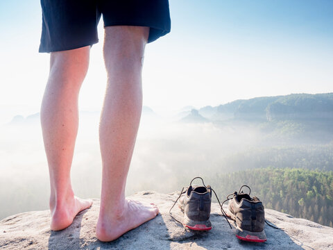 Barefoot legs with hairy calves of man stay at to removed running shoes