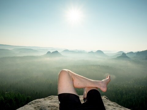 Crossed male barefoot legs of man relax on mountain summit.