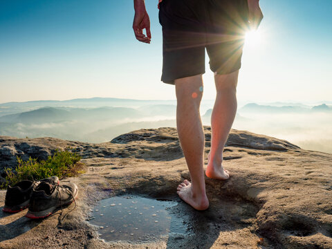 Hiker next to taken off shoes and water puddle on sandstone rock edge enjoy  view