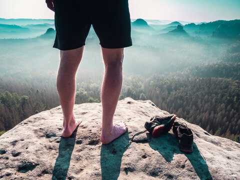 Barefoot slender legs with hairy calves of a male runner standing next to removed sweaty running shoes on a rocky edge above a long deep vally in nature park.
