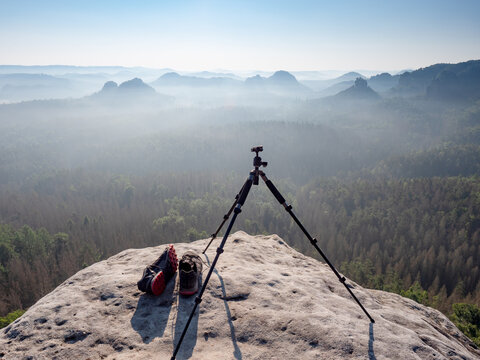 Modern professional travel tripod and black red sneakers on mountain summit.