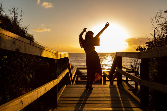 silhouette of young woman with arms in the air celebrate life against sunset at the beach