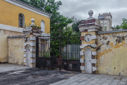 Rusty gates and falling off plaster of military-economic warehouses