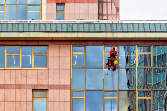 An industrial climber in a red uniform washes windows at a high altitude of an office building