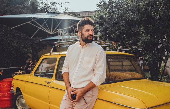 Handsome beard man make photo on film old camera, street hipster, outdoor portrait, photographer, yellow old car, vintage photo,