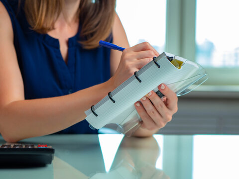 Woman with notebook. Thick diary in woman hand. Notepad with accountant hand. Hands with notebook close-up. She is counting something and writing it down. Accountant career. Office worker calculator