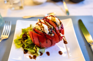 Big red french tomato served with fresh mozzarella cheese, basil pesto and creme balsamico as...