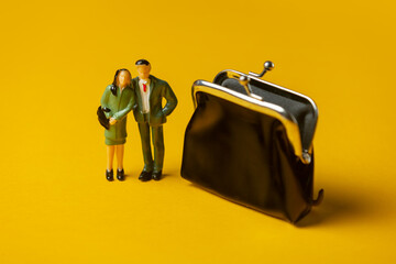 Fototapeta miniature figures of a man and woman next to classic wallet on yellow background obraz