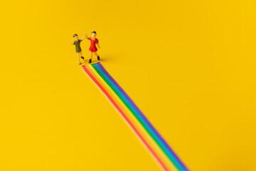 Fototapeta little girl and boy figures on the LGBT rainbow path obraz