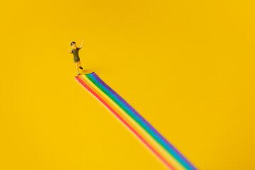 Fototapeta little boy figure stand on rainbow LGBT strip on yellow background obraz
