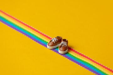 Fototapeta Little shoes on LGBT rainbow strip on yellow background obraz