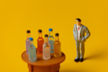 Fototapeta miniature figure of a man with alcohol bottles in front of him obraz