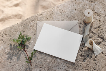 Fototapeta Summer wedding stationery mock-up. Blank greeting card, invitation with craft envelope and silk ribbon. Green lentisk branch on beige concrete background in sunlight. Blurred sand. Flat lay, top view. obraz