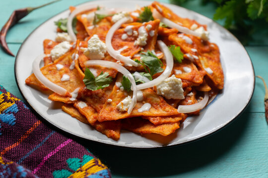 Mexican food. Red chilaquiles with cheese and sour cream on turquoise background