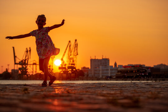 Little girl dancing during sea sunset. Silhouttes of industrial cranes on sea port Varna, Bulgaria