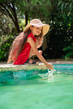 Portrait of young beautiful woman playing with water. Playful little girl in a park.