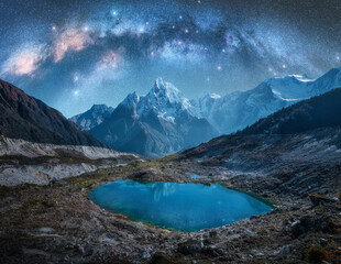 Milky Way over snowy mountains and lake at night. Landscape with snow covered high rocks, starry sky, reflection in water in Nepal. Sky with stars. Bright milky way in Himalayas. Space and nature