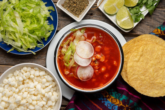 Mexican food. Red pozole with chicken on wooden background