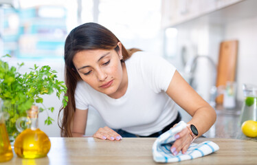 Fototapeta Young latino woman cleans the kitchen table at her house obraz