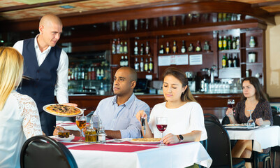 Portrait of polite smiling waiter serving pizza to friendly company in cozy pizzeria