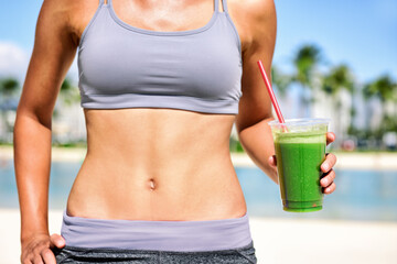 Fototapeta Green juice smoothie healthy detox diet weight loss fit woman drinking juice on outdoor beach summer lifestyle. Abs stomach and plastic cup. obraz
