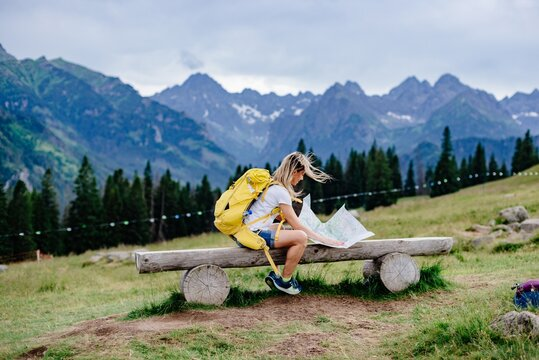 Female traveler with yellow backpack sitting on a bench watching a map on a sunny day in the mountains.