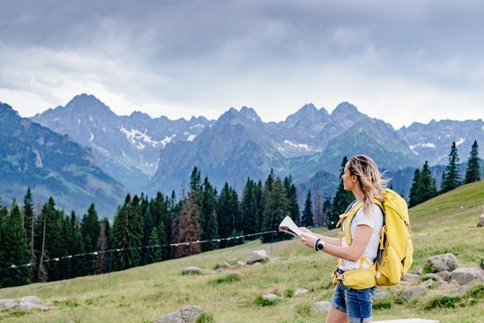Adventurous girl navigating in with a topographic map in the beautiful mountains.
