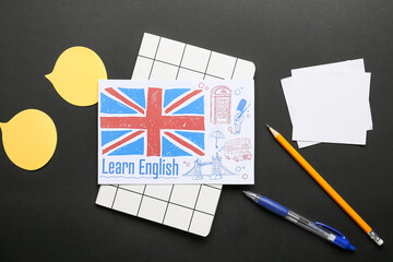 Stationery and paper with picture of UK flag on dark background. Concept of learning English