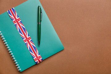 Notebook, pen and ribbon in colors of UK flag on color background. Concept of learning English