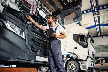 Fototapeta Hardworking tattooed bearded mechanic leaning on truck and checking on motor while standing in garage of import and export firm. obraz