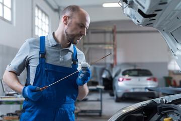 Fototapeta Mechanic checking a car's oil level in the garage obraz