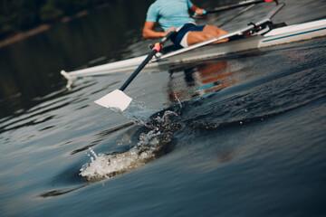 Fototapeta Sportsman single scull man rower rowing at competition boat regatta. Close up paddle splash water obraz
