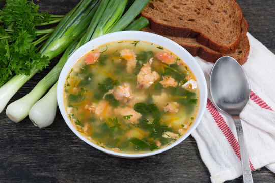Bowl of clear salmon soup, greens, bread, spoon on napkin