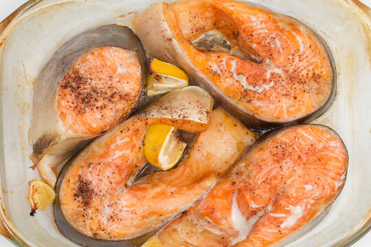Baked pieces of rainbow trout in glass dish, top view