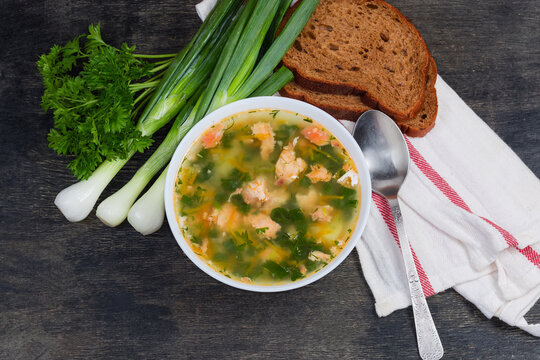 Top view of clear salmon soup, greens, bread and spoon
