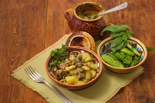 Meat stewed with vegetables in clay pot, lightly salted cucumbers