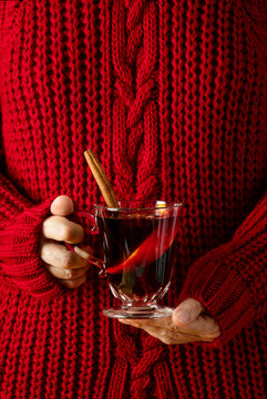 Woman wearing cozy red pullover holding a cup of mulled wine