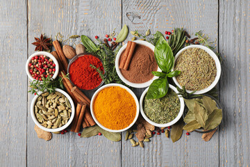Fototapeta Different natural spices and herbs on grey wooden table, flat lay obraz