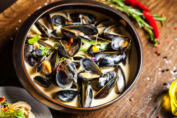 Fototapeta Blue mussels in cream wine sauce. Delicious healthy Italian traditional food closeup served for lunch in modern gourmet cuisine restaurant obraz
