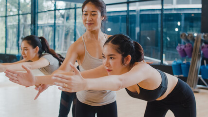 Fototapeta Young Asian sporty attractive people practicing yoga lesson with instructor. Asia group of women exercising healthy lifestyle in fitness studio. Sport activity, gymnastics or ballet dancing class. obraz