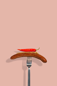 Cover page with single grilled sausage with mustard on it and hot chili pepper put on a metal modern fork at solid pink color background with copy space for text. Concept of street food and cuisine.